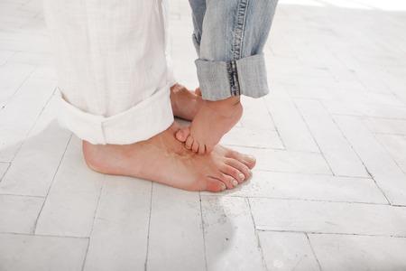 Der Vater und seine 9 Monate alten Sohn Füßen, klein und groß auf weißem Hintergrund zu Hause