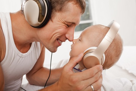 nine  months: young father with his nine months old som on the bed at home on white background. Father and son wearing headphones