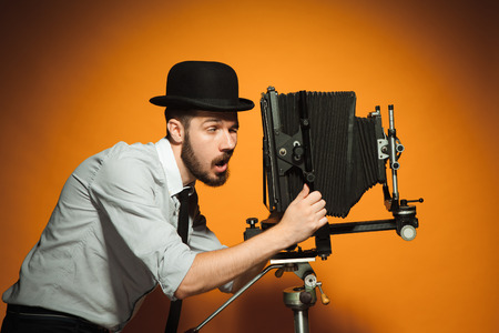 squinting: Young positive man in hat as photographer squinting and looking into the lens of  retro camera on an orange background