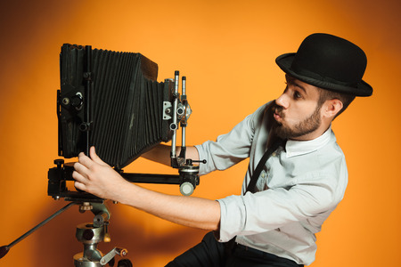 side view of young positive man in hat as photographer with retro camera on an orange background