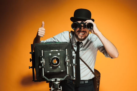 looking through frame: Young man in hat as photographer with retro camera looking through binoculars on an orange background