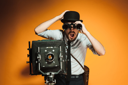 looking through an object: Young man in hat as photographer with retro camera looking through binoculars on an orange background