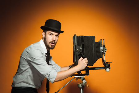 afraid man: side view of young  afraid man in hat as photographer with retro camera on an orange background Stock Photo