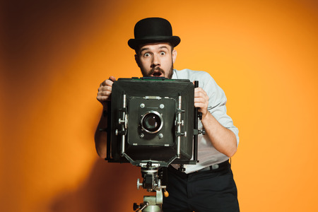 photo studio: Young  afraid man in hat as photographer with retro camera on an orange background Stock Photo