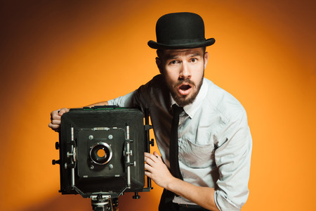 panicked: Young  afraid man in hat as photographer with retro camera on an orange background Stock Photo