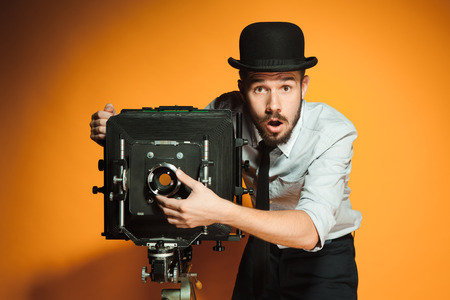 Young surprised man in hat as photographer with retro camera on an orange background Stock Photo