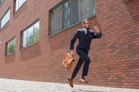 Jonge zakenman met een koffer en een bril lopen in een straat in de stad op een achtergrond van rode bakstenen muur Stockfoto