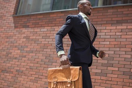 hombre rojo: El hombre africano como hombre de negocios negro con un malet�n corriendo en una calle de la ciudad sobre un fondo de pared de ladrillo rojo Foto de archivo