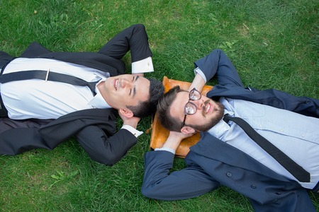 field work: The two happy young businessmen in a suites lying on the green grass, top view. The one man is European, other is Chinese