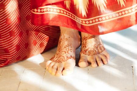女性の足、mehendi 伝統装飾、特殊塗料、茶色ヘナで耐震設計のインド映像。 白い背景の上インド赤ドレス 写真素材