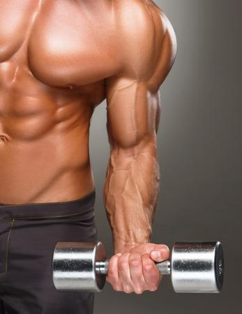 culturista: Primer plano de un apuesto hombre de poder atlético hombre culturista haciendo ejercicios con mancuernas. Musculoso cuerpo fitness en el fondo oscuro.