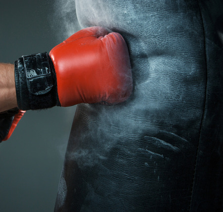 Zbliżenie ręki bokser w momencie uderzenia na worek bokserski na czarnym tle