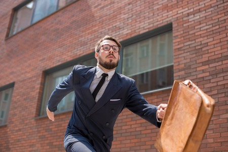 jumping businessman: Young businessman with a briefcase and glasses running in a city street on a background of red brick wall Stock Photo
