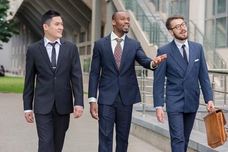 profesionistas: Retrato de múltiples negocios étnicos team.Three hombres sonrientes caminando contra el fondo de la ciudad. El hombre es europeo, otra es chino y afroamericana.