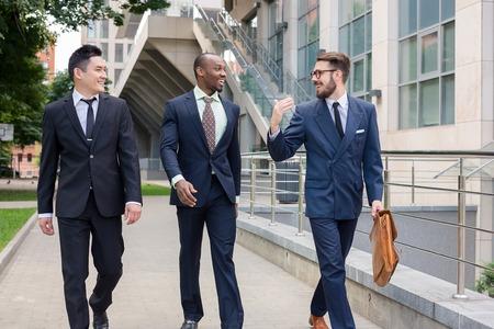 Retrato de múltiples negocios étnicos team.Three hombres sonrientes caminando contra el fondo de la ciudad. El hombre es europeo, otra es chino y afroamericana.