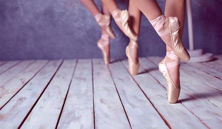 De close-up voeten van een drie jonge ballerina's in pointe schoenen tegen de achtergrond van de houten vloer