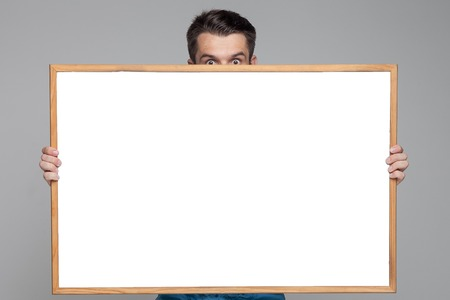 visible: The surprised man showing empty white billboard or banner on gray background. Only his eyes are visible