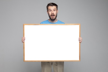 The surprised man showing empty white billboard or banner on gray background