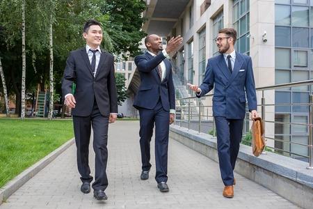 relaciones humanas: Retrato de múltiples negocios étnicos team.Three hombres sonrientes caminando contra el fondo de la ciudad. El hombre es europeo, otra es chino y afroamericana.