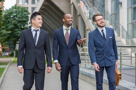 Portrait of multi ethnic business team.Three smiling men walking against the background of city. The one man is European, other is Chinese and African-American.