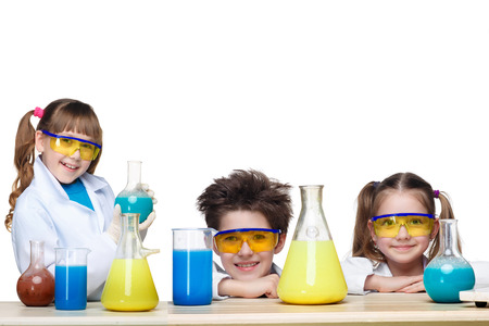 chemistry lesson: The three cute children  as chemists at chemistry lesson making experiments isolated on white background