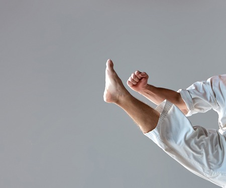 karate fighter: Man in white kimono training karate over gray background. close-up of arm and leg athlete during impact Stock Photo