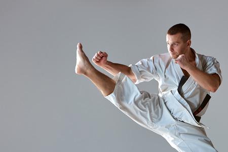 hombre deportista: Hombre en blanco karate kimono formación sobre fondo gris. primer plano de un brazo y la pierna del atleta durante el impacto
