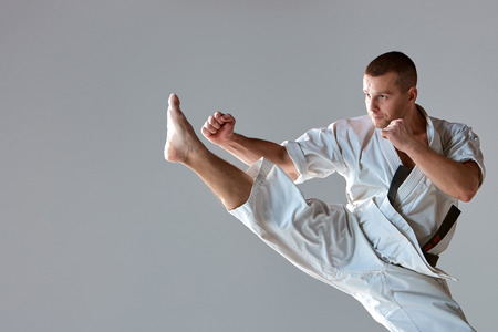 Man in white kimono training karate over gray background. close-up of arm and leg athlete during impact Imagens