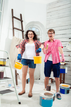 renovating: Funny and crazy smiling young couple with paint cans in their hands and paint  brush doing repair at home. White background