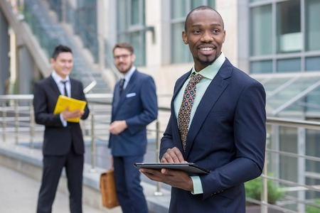 Portrait of multi ethnic business team. Three happy smiling men standing against the backdrop of the city. The one man is African-American, other is Chinese and European. concept of business success