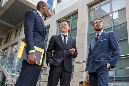 young worker: Portrait of multi ethnic business team.Three smiling men standing against the background of city. The one man is European, other is Chinese and African-American.
