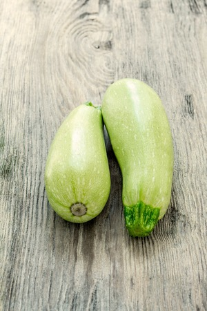phallic: The two  green  zucchini on wooden background