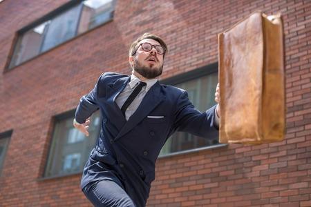 Jeune homme d'affaires avec une mallette et des verres en cours d'exécution dans une rue de la ville sur un fond de mur de briques rouges. concept de carrière rapide