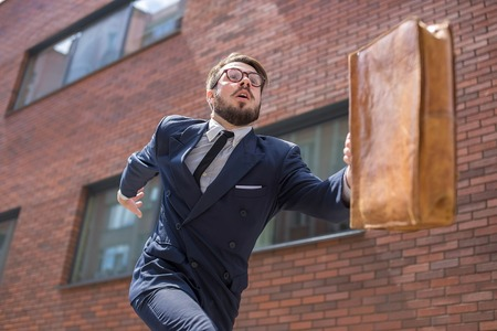 Jonge zakenman met een koffer en een bril lopen in een straat in de stad op een achtergrond van rode bakstenen muur. Het concept van de snelle carrière