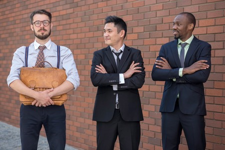 formations: Portrait of multi ethnic business team.Three smiling men standing against the background of red brick wall. The one man is European, other is Chinese and African-American. the concept of old and new business formation
