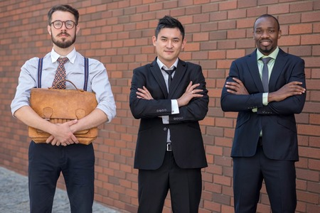 old asian: Portrait of multi ethnic business team.Three smiling men standing against the background of red brick wall. The one man is European, other is Chinese and African-American. the concept of old and new business formation