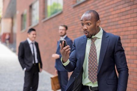 Portrait der multi-ethnischen Business-Team. Drei glückliche lächelnde Männer stehen vor dem Hintergrund der Stadt. Das überrascht African-American Mann am Telefon zu sprechen, andere chinesische und europäische. Konzept für den wirtschaftlichen Erfolg