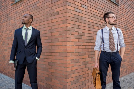black professional: Portrait of multi ethnic business team. Two men standing against the backdrop of the city. The one man is African-American, other is European. concept of business success