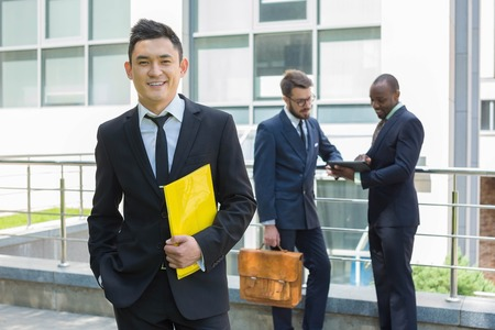 happy business team: Portrait of multi ethnic business team. Three happy smiling men standing against the backdrop of the city.  The foreground of a Chinese  man