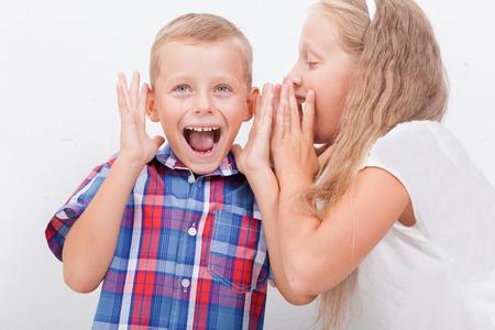 teen boys: Teenage girl whispering in the ear of a secret teen boys on white background