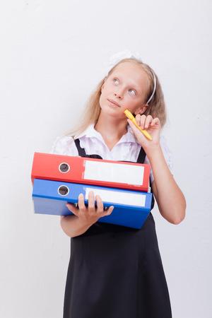 girl notebook: Schoolgirl  holding pen and folders in her hands over white background
