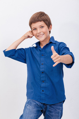 young male model: Happy young teen boy with calling gesture over white background