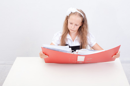 beautiful preteen girl: Schoolgirl  holding red folder and reading documentation over white background