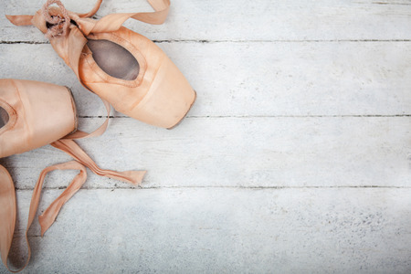 old items: The old pointe shoes on white wooden background, copyspace image
