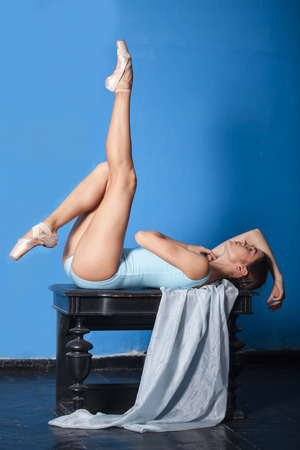 female pose: young modern ballet dancer sitting and posing on blue room background