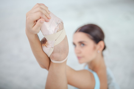 ballerina shoes: young modern ballet dancer posing against the white room background. arm and leg close up