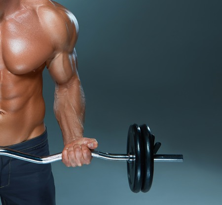 shirtless men: Portrait of super fit muscular young man working out in gym with barbell on gray background, copyspace image Stock Photo