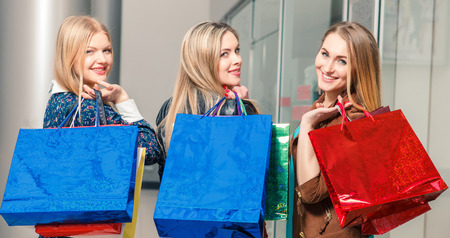 la compra, venta, gente feliz y el turismo concepto - tres hermosas chicas con bolsas de la compra miró hacia atrás en el centro comercial