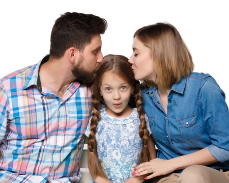 girl sitting: A happy family isolated on  white background.Parents kissing baby Stock Photo