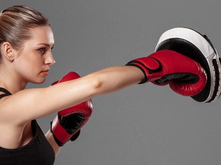 female boxing: beautiful woman with the red gloves is boxing on gray background